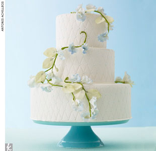 Round, three-tiered, quilted fondant wedding cake accented with sugar-made vines and pale blue flowers by Gail Watson Custom Cakes, GailWatsonCake.com