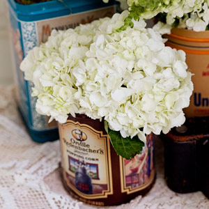 Clusters of white hydrangea were displayed in antique food tins.