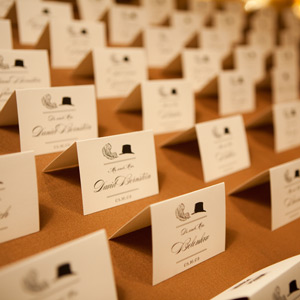 Guests found their names and table assignments on tented cards with illustrations -- for the ladies and top hats for the men (couples' cards had both).
