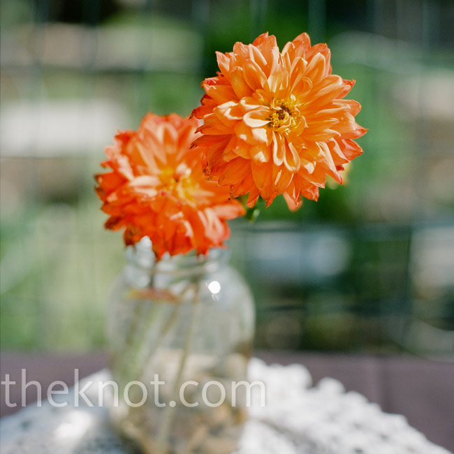 The couple decided to embrace the rustic atmosphere of their reception venue in the décor. For centerpieces, they used antique Mason jars filled with orange daisies, mums, and peonies.