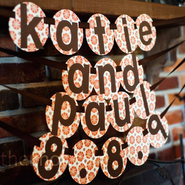 A DIY wedding banner with Katie and Paul's names and wedding date hung on the mantel place of the ranch. The couple tried to incorporate as many personalized details as they could to give their wedding a low-key, family picnic atmosphere.