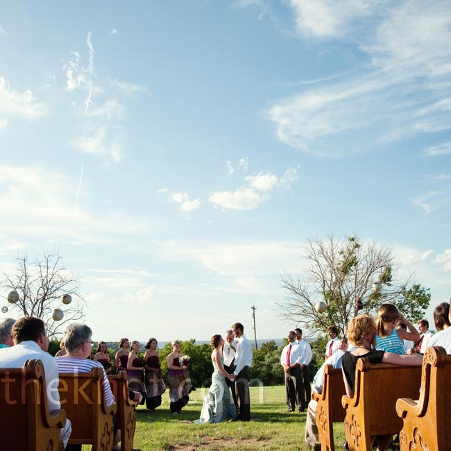 Katie and Paul exchanged vows on the front field of Hidden Falls Ranch. Two trees hung with paper lanterns marked the altar space, but otherwise the only decoration was the breathtaking view. They used a few old church pews from the camp chapel for seating.