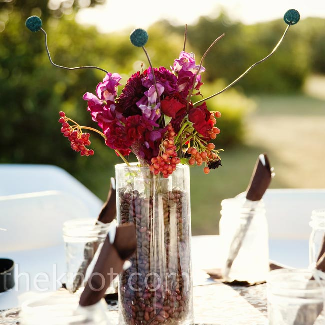 Each table at the indoor/outdoor reception had a different centerpiece for an eclectic look. There was a mix of lanterns, bottles filled with peacock feathers and berries, and floral arrangements with cases filled with coffee beans.