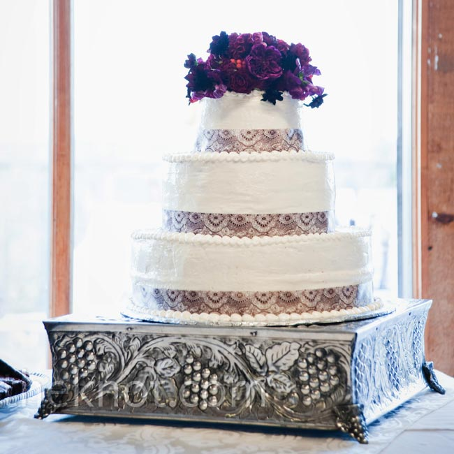 The three-tiered spice cake was frosted in off-white buttercream and decorated with a lace ribbon along the bottom of each tier. Fresh flowers that matched the bridesmaid dresses topped the confection. The couple also served brownies and vanilla ice cream for Paul in place of a groom's cake.