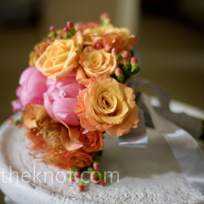 Anda carried a bright bouquet of pink and orange roses, coffee berries, peonies, pincushion protea, and mini calla lilies.