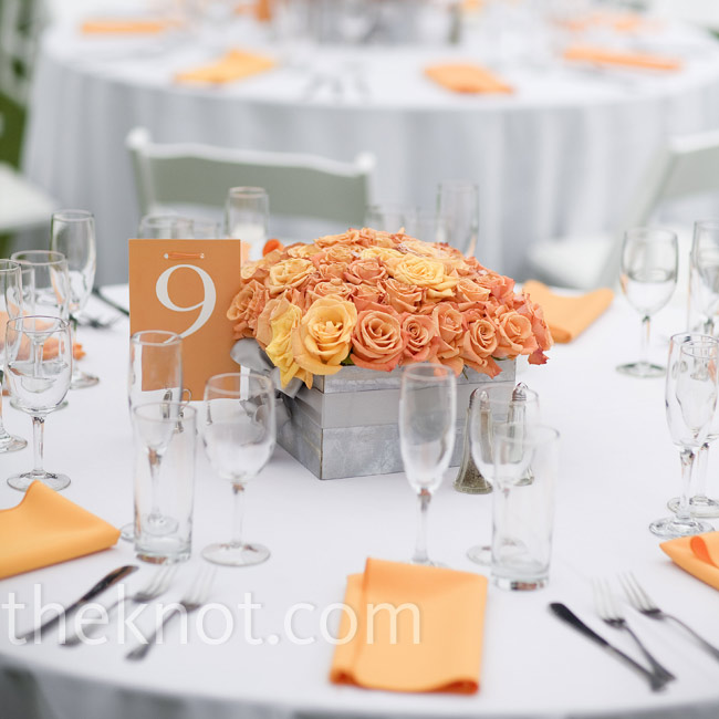 For the outdoor celebration, Anda and Ariel had orange centerpieces of roses packed into square silver containers.