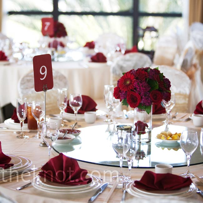 Anda and Ariel used a bold red color palette when decorating their second reception, including dramatic red rose and gerbera centerpieces and modern table number cards.