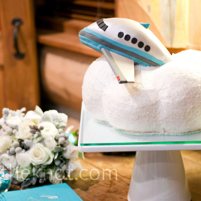 An edible airplane peaked its nose out through a cake shaped like a cloud.