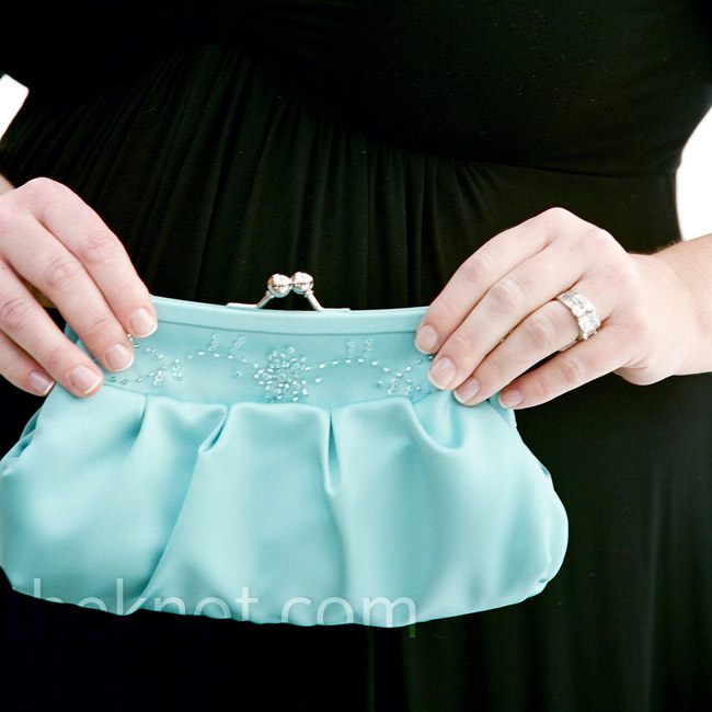 "Instead of a bouquet, Ashley had her ""flight attendant"" carry an aqua clutch -- packed with Patrick's ring, lip balm, tissues, and other necessary items!"