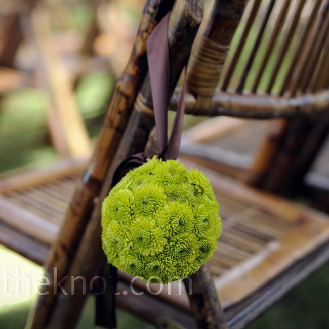 Hanging green pomanders hung from the ceremony chairs lining the aisle.
