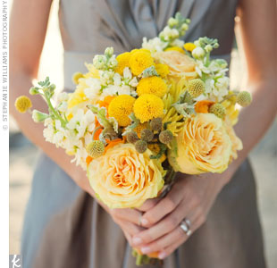 The bridesmaids carried a mix of  yup -- yellow blooms, incuding cabbage roses, mums, billy balls, and ranunculus. The bride carried similar flowers in white.