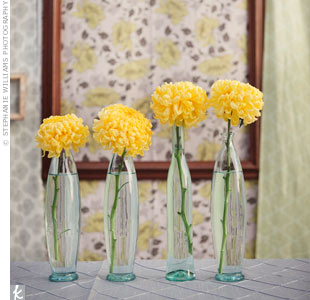 Tables were topped with small bundles of yellow flowers, yellow candles, a lantern and gray-and-white place settings.