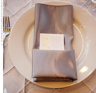 Yellow menu cards wrapped in silver napkins marked each place.