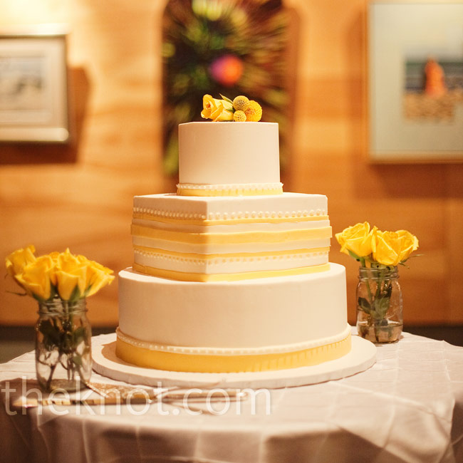 Three white tiers -- alternating between round and square -- were decorated with yellow ribbons and fresh flowers.