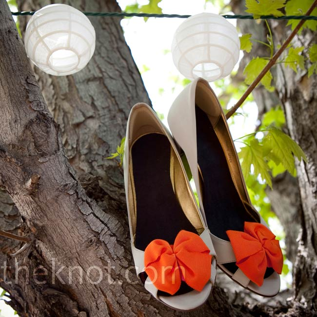 Alanna added a pop of color to her bridal style with a pair of whimsical gray satin, peep-toe heels adorned with bright orange bows.