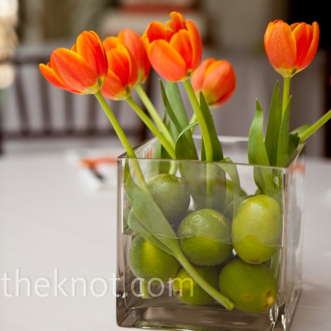 There were two different centerpieces displayed on the reception tables. One was a modern mix of bright orange tulips and fresh green limes displayed in square vases. The other was white tulips with sliced oranges covering up the stems.
