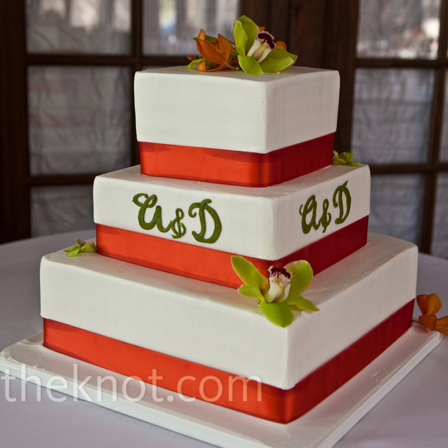 The bride and groom chose three square tiers for a modern cake with clean lines. Orange ribbon wrapped around the base of each tier while green and orange orchids and a green monogram personalized the confection.