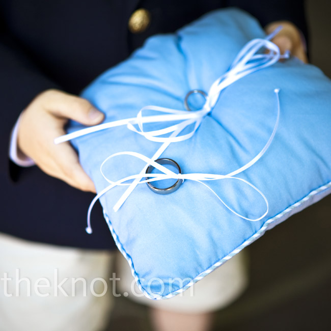 To match the wedding colors, the couple's nephew carried a blue ring pillow with long ribbons to attach the rings. Both ring bearers wore navy blazers with khaki shorts and Chuck Taylors, mirroring the look of the groomsmen and groom.