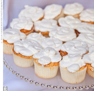 The bride isn't a fan of cake or frosting, so the couple served light and fluffy angel food cupcakes topped with various designs of white whipped cream.