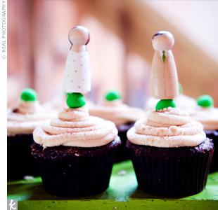 To keep the day casual, the couple served vegan chocolate peanut butter cupcakes topped with chartreuse balls and displayed on tall tower. A miniature bride and groom, painted to match the couple, topped the display.