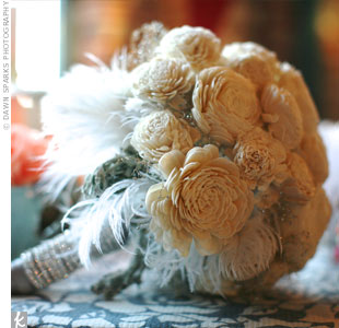"The bride's keepsake bouquet consisted of white balsa wood flowers, dried baby's breath, dusty miller and elegant white ostrich feathers and was wrapped with a pewter ribbon and rhinestone sash. ""It was unbelievable,"" she says."