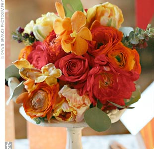 Though the couple used mostly paper and dried floral arrangements, the bridesmaids carried bouquets of richly colored dahlias, roses, ranunculus, parrot tulips, Mokara orchids, boronia, and silver-dollar eucalyptus.