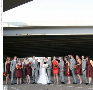 The wedding party brought the colors of the day together with berry-colored bridesmaid dresses in different styles. The matron of honor stood out in a persimmon-colored knee-length dress while the men wore sharp gray to match the groom.