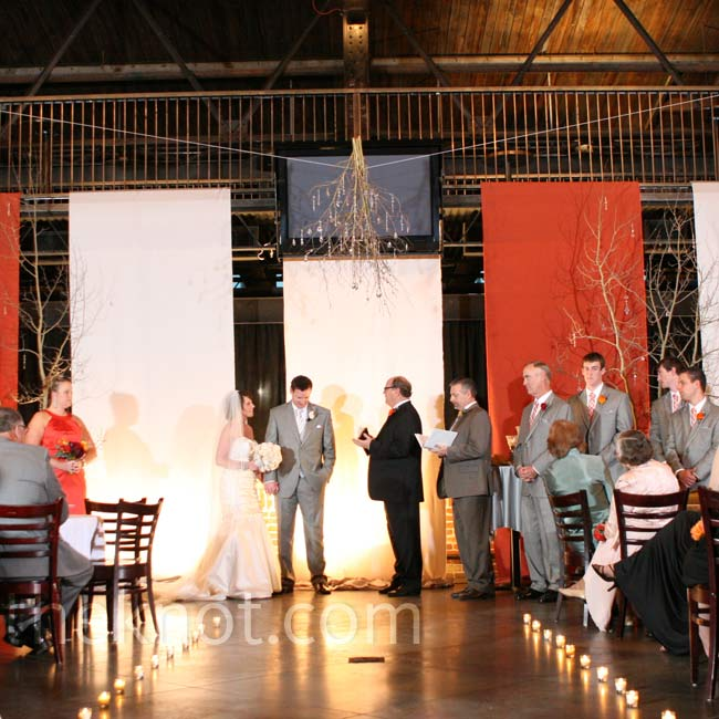 The couple exchanged vows between two potted Aspens and beneath a tree branch chandelier made by the bride. Five illuminated fabric panels in the wedding colors hung as a backdrop.