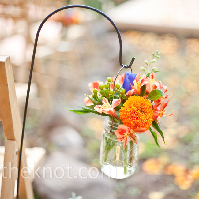 Mason jars filled with orange and purple wildflowers hung from shepherd's hooks along the wedding aisle.