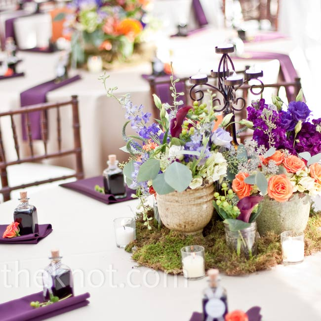Orange, purple, and green blooms were arranged in rustic pots, surrounded by votive candles and displayed on beds of moss.