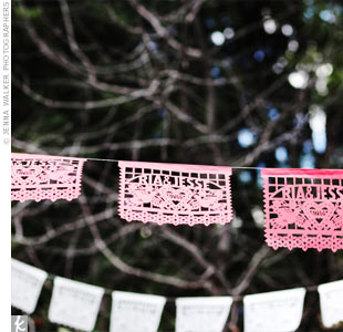 Bright papel picado, or Mexican paper banners, were personalized with the couples names and surrounded by bright paper lanterns.