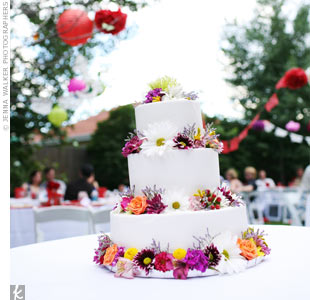 The three-tiered white buttercream cake covered in fresh flowers was a must have for Ria and Jesse.