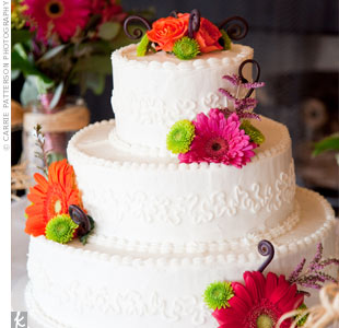 Erin and Aaron cut into a three-tiered carrot cake covered in white buttercream. Orange, green, and pink flowers tied the confection in with their wedding decor.