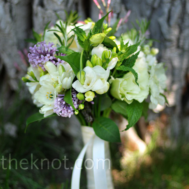 "To achieve a ""just picked"" feel, Lindsay's florist used lots of wildflowers and lilacs for her white with flecks of purple bouquet."