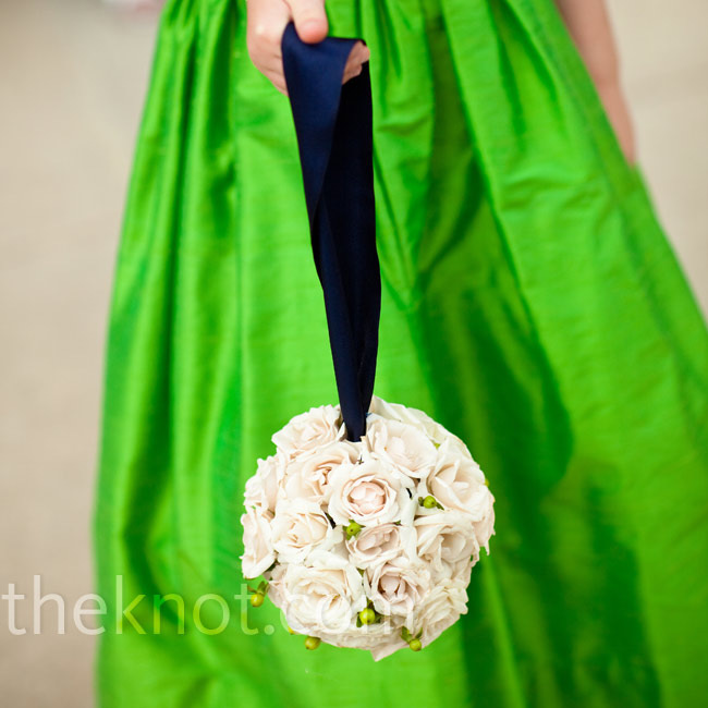 The flower girl carried a pomander of white Canadian sweetheart roses strung on a navy ribbon.
