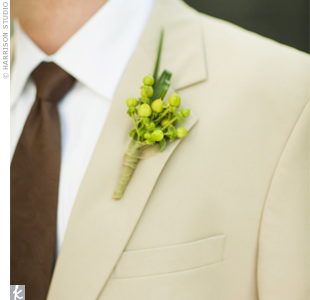 The groomsmen all wore these green hypericum berries and Brad wore a yellow orchid to match Michelle&#39;s bouquet.