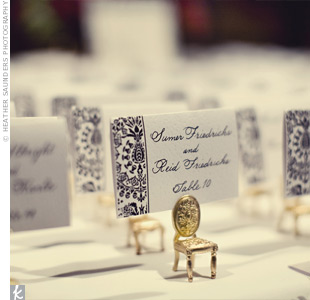 "Miniture vintage-style gold chairs held the black-and-white escort cards. Playing on words, the couple added a sign that read, ""Please take a seat."""