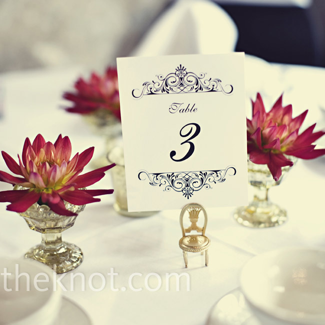 The same mini chairs that held the escort cards held the table numbers, which were printed on white cards with intricate scroll borders. Each table number was surrounded by three mini urns, each holding one dahlia flower.