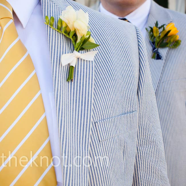 In keeping with the colors of the day, the guys wore seersucker jackets and white yellow freesia boutonnieres tied together with navy-striped ribbon.