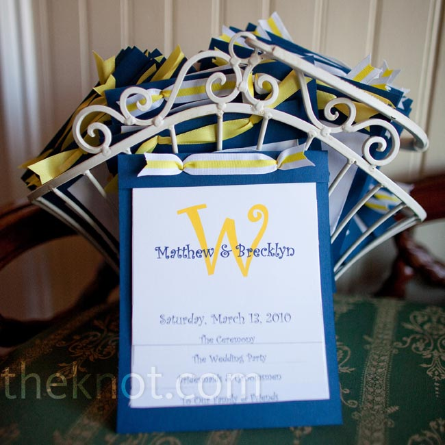 "Brecklyn and her bridesmaids backed the layered white linen program on blue cardstock. The ""W"" on the top of the program resembled the floral arrangement that hung on the front door of the House Plantation."