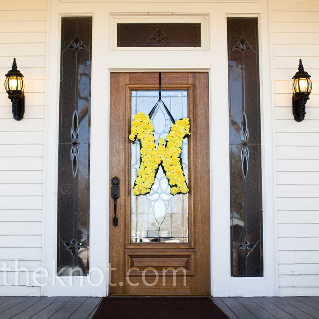 "A giant ""W"" of yellow carnations, for Brecklyn and Matt's newly shared last name, hung from the front door of the House Plantation. In keeping with the theme, Brecklyn included the yellow ""W"" in a fun curly font on the invitations and ceremony programs."