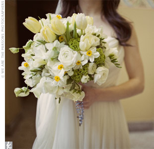 A florist designed Eagen's loose, natural bouquet out of white ranunculus, white sweet pea, tulips, narcissus, viburnum and variegated pittosporum.