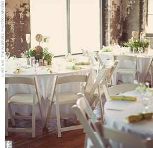 Eagen wanted low-key centerpieces that worked with their urban loft space, so her sister, aunts, mom, and bridesmaids helped pull together the tabletop decor, which consisted of potted plants, rainbow lollipops, hurricane vases, paper lanterns, and candles.
