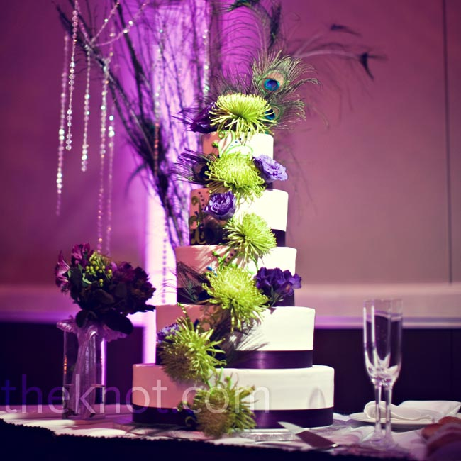 Green spider mums and purple lisianthus decorated the all-white cake tiers. The dessert was topped off with a giant peacock feather.