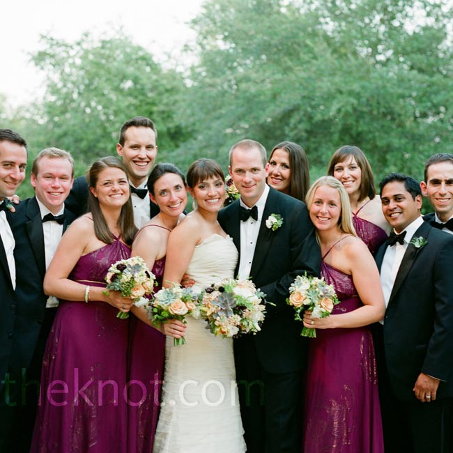 Floor-length berry-colored silk bridesmaid dresses coordinated nicely with the groomsmen's black tuxes and bow ties.