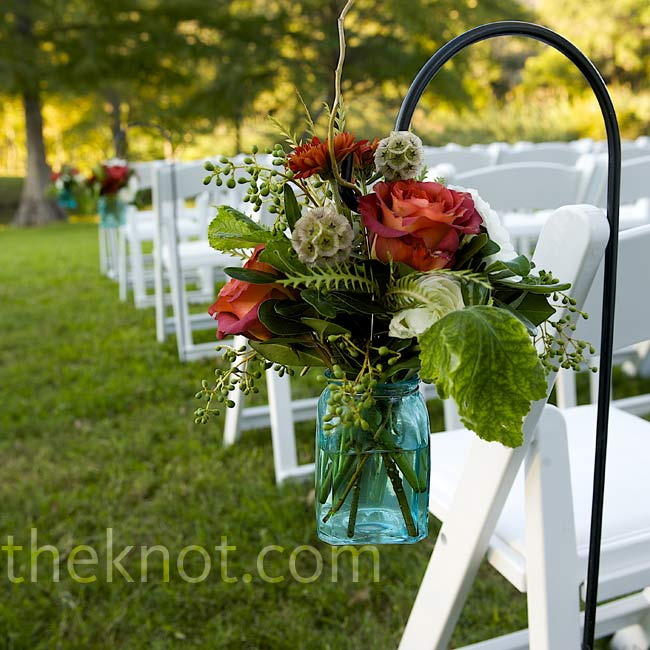 Arrangements of roses and greens hung from waist-high wrought iron shepherd's hooks at the ceremony.