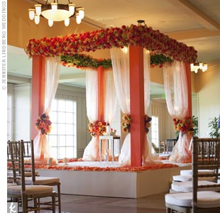 The huppah's bright orange pillars were draped in chiffon and topped with orange roses, Mokara orchids, cymbidiums, and hydrangeas.