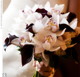 Kim's florist combined dark purple calla lilies with white cymbidium orchids in keeping with the theme.