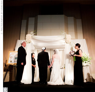 Their huppah was draped in ivory organza and topped with dozens of white Vendela roses and dendrobium orchids.