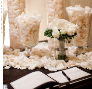 The guest book was displayed on a table with glass vases filled with white rose petals. Guests later tossed the petals on the couple as they left the reception.